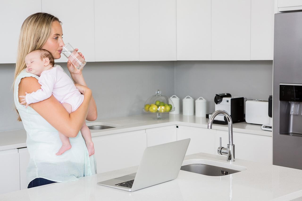 Mutter trinkt Wasser in der Küche mit Kind